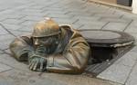 Bronze figure of a Sewer worker peeks through the manhole in Bratislava