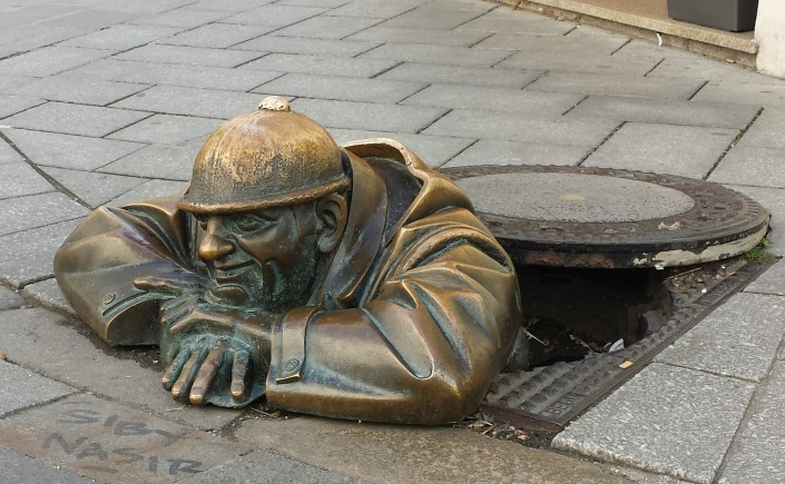 Bronze figure of a Sewer worker peeks through the manhole in Bratislava